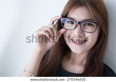 Young asian girl smiling and glasses in black shirt - stock photo