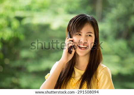 Young Asian girl use mobile phone for search information in the garden. - stock photo