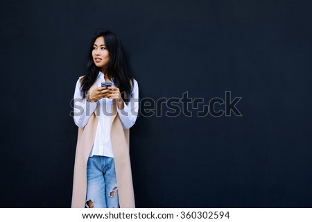 Young Asian girl using smart-phone on a black wall background with copy space for your text or design - stock photo