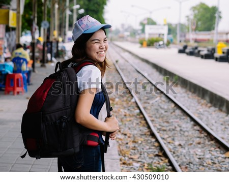 young asian girl waiting for the train in station with smile and happy, single alone woman at train station with back pack for travel