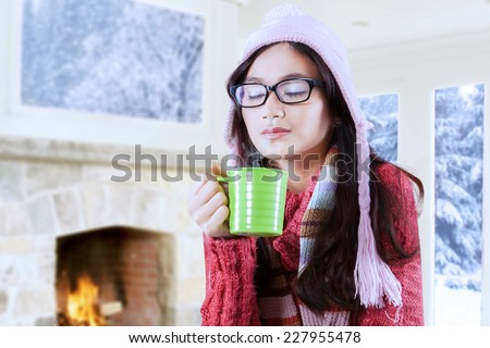 Young asian girl wearing sweater and enjoy hot drink at home with winter background - stock photo