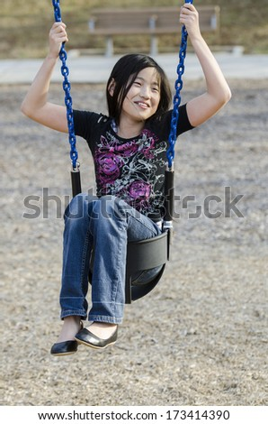 young Asian girl wedged in a kiddie swing - stock photo
