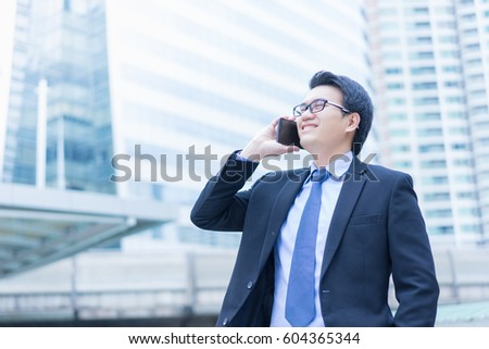 Young asian handsome businessman and glasses using smartphone with smiling at business district