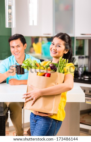Young Asian handsome woman coming home from grocery shopping - stock photo