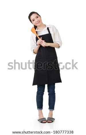 Young Asian housewife hold a spatula in apron, full portrait isolated on white background.