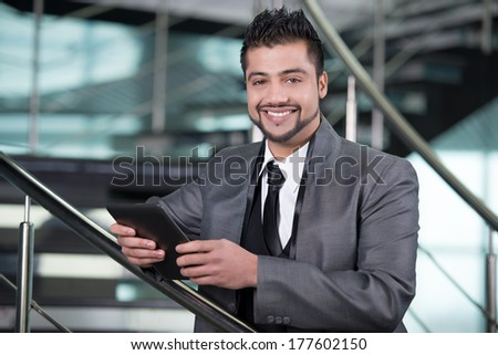 Young Asian Indian businessman standing on office background and holding a tablet in hands - stock photo