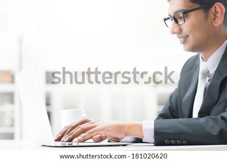 Young Asian Indian businessman using a  laptop  or notebook computer during office break at cafe, relaxing with a cup of coffee. India male business man, real modern office building as background. - stock photo