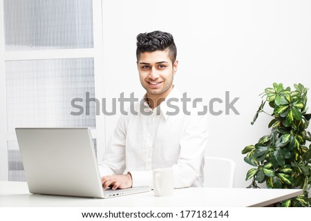 Young Asian Indian Businessman working on laptop in office - stock photo