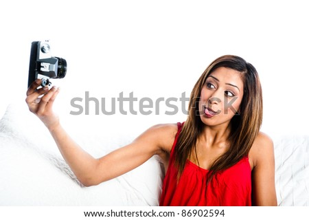 Young Asian Indian girl with old camera, taking photos of herself, sticking tongue out to camera, - stock photo