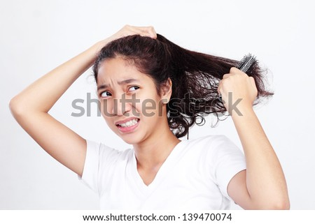 Young asian lady with an unpleasant facial expression while brushing her curly hair. - stock photo
