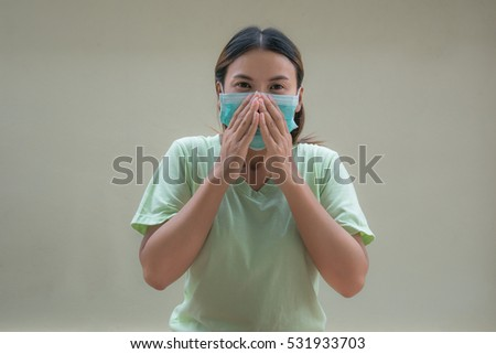 Young Asian long-haired woman in protective medical mask.