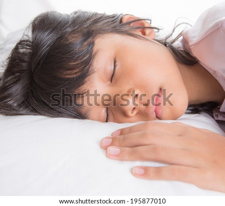Young Asian Malay girl sleeping peacefully on her bed