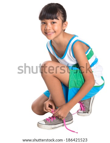 Young Asian Malay girl with athletic attire tying her shoelace over white background