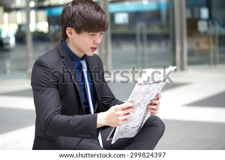 Young Asian male business executive reading newspaper