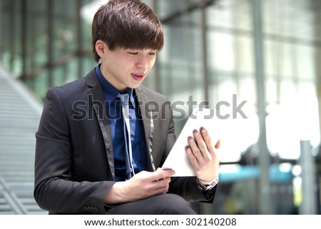Young Asian male business executive using tablet PC and smiling