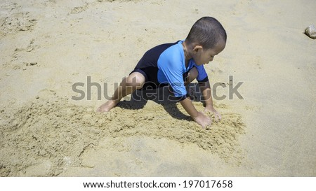 Young Asian male kid wearing black and blue swimsuit playing with sand on a tropical beach