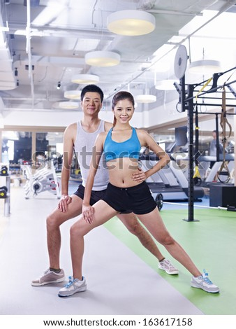 young asian man and woman working out together in gym.