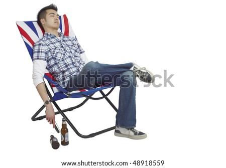 Young Asian man asleep in a chair with a remote in his hand and beers on the floor. - stock photo