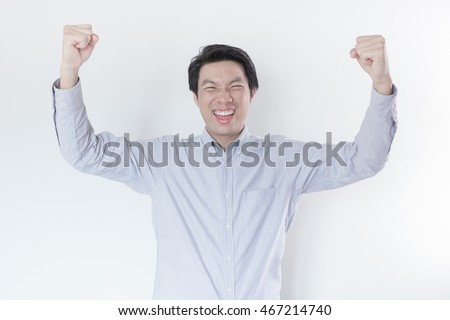 Young Asian man celebrating his success on white background
