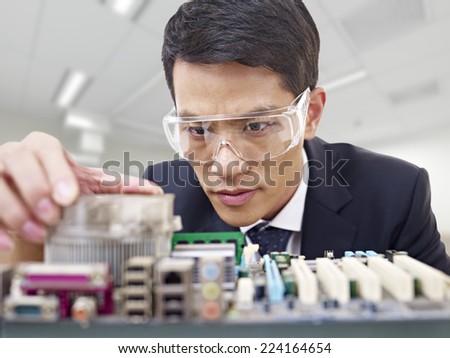 young asian man fixing computer with protective eyewear - stock photo