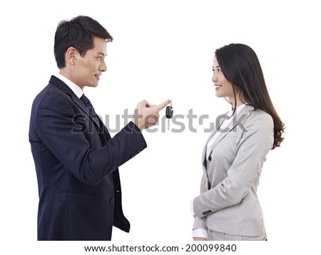 young asian man handing car key to young asian woman, isolated on white. - stock photo
