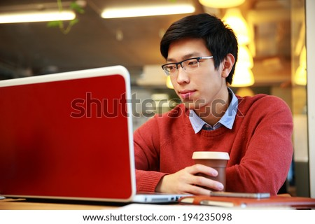 Young asian man in glasses working on laptop and holding cup of coffee - stock photo