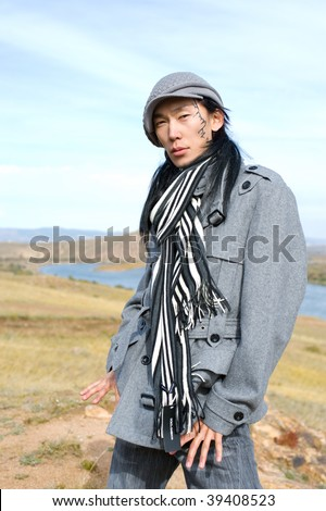 Young asian man in grey coat, cap and striped black-and-white scarf. The tracery on his cheek is his name Chinghis in ancient Mongolian.