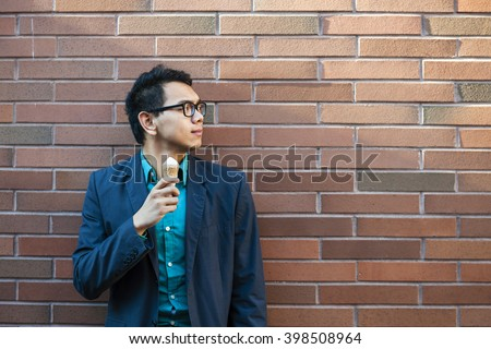 Young asian man in his twenties with ice cream while standing alone near brick wall outside looking to the side - stock photo