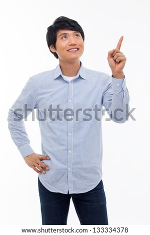 Young asian man indicated upside isolated on white background.