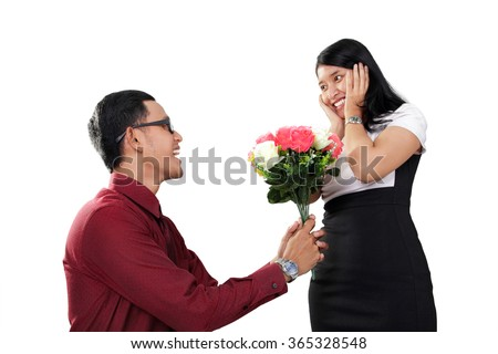Young Asian man kneel down and gives flowers to her surprised girlfriend, isolated on white background - stock photo