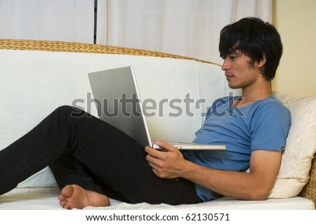Young Asian man laying on sofa using computer for social networking
