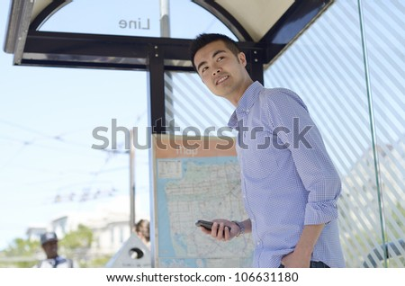 Young Asian man looks out from a bus stop with his phone in hand - stock photo