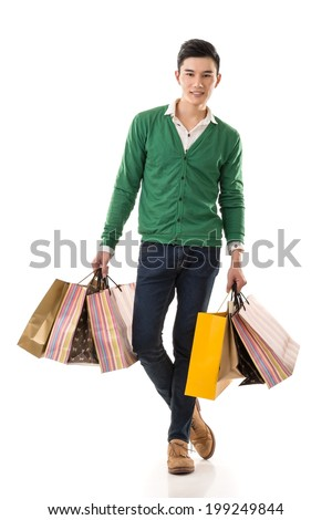 Young Asian man shopping and holding bags, full length portrait isolated on white background. - stock photo