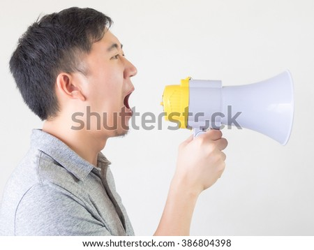 Young Asian man shouting with a megaphone isolated white background - stock photo