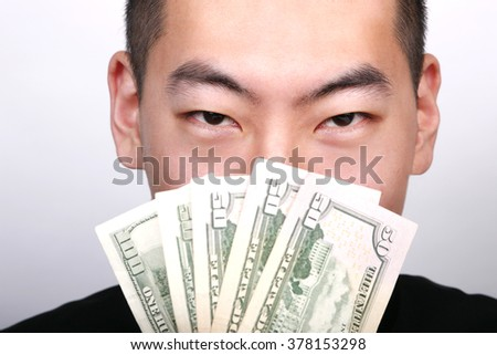 Young Asian man showing American currency. - stock photo