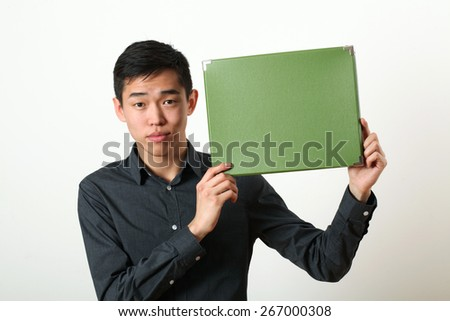 Young Asian man showing green copy space box and looking at camera - stock photo
