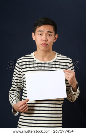 Young Asian man showing white copy space page and looking at camera - stock photo