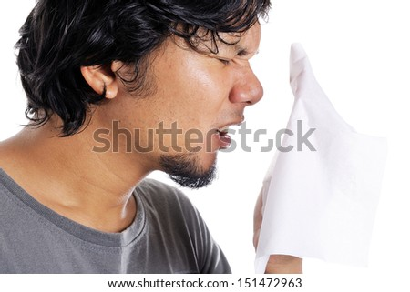 young asian man sneezing to tissue paper