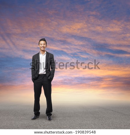 young asian man standing in front of late afternoon sky