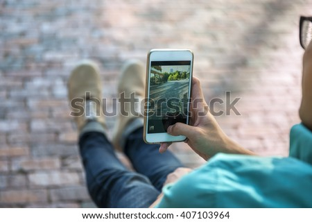 Young asian man taking photo of street and his feet with smartphone
