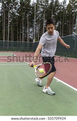 Young Asian Man using single handed backhand on outdoor tennis court