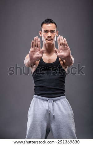 Young asian man workout over grey background - stock photo