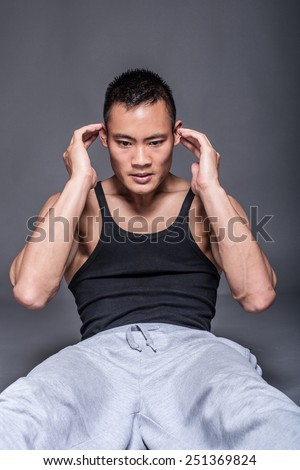Young asian man workout over grey background - abdominal crunch - stock photo