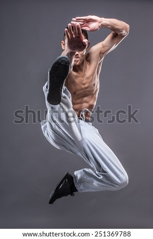 Young asian man workout over grey background karate jump kick - stock photo