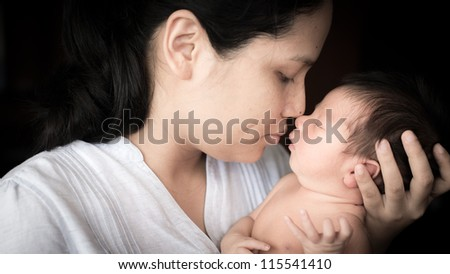 Young Asian mother lovingly holds her newborn baby boy (5 days old) - stock photo
