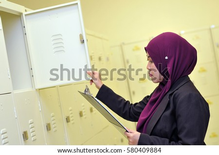Young Asian Muslim business woman  holding file document while stock checking. Beautiful Muslim women.