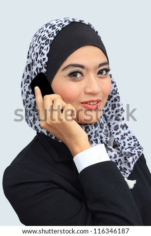 Young asian muslim business woman talking to the mobile phone while looking to the camera