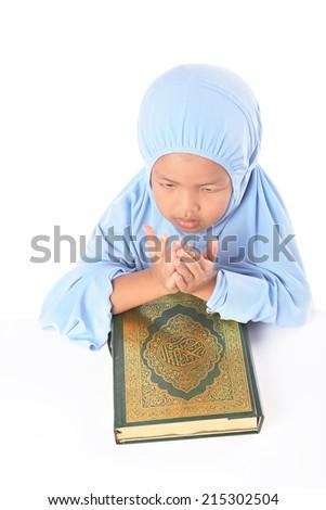 Young Asian Muslim girl in blue hijab pray before reading Al Quran - stock photo