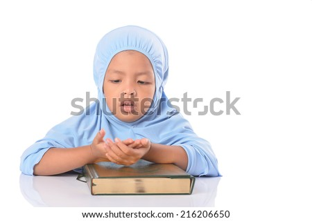 Young Asian Muslim girl in blue hijab reading Al Quran, over white background. - stock photo