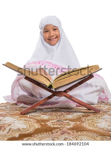 Young Asian Muslim girl in white hijab reading Al Quran on a prayer mat over white background. - stock photo